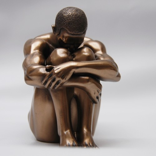 Beautiful decorative sculpture of a man sitting in resin bronze color