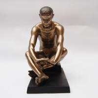 Beautiful decorative sculpture of a man sitting on black base in bronze color
